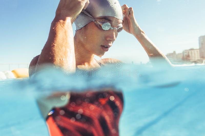 Professional swimmer taking a break. Close up of young woman swimmer inside the pool adjusting her goggles. Professional swimmer taking a break while training in royalty free stock photos