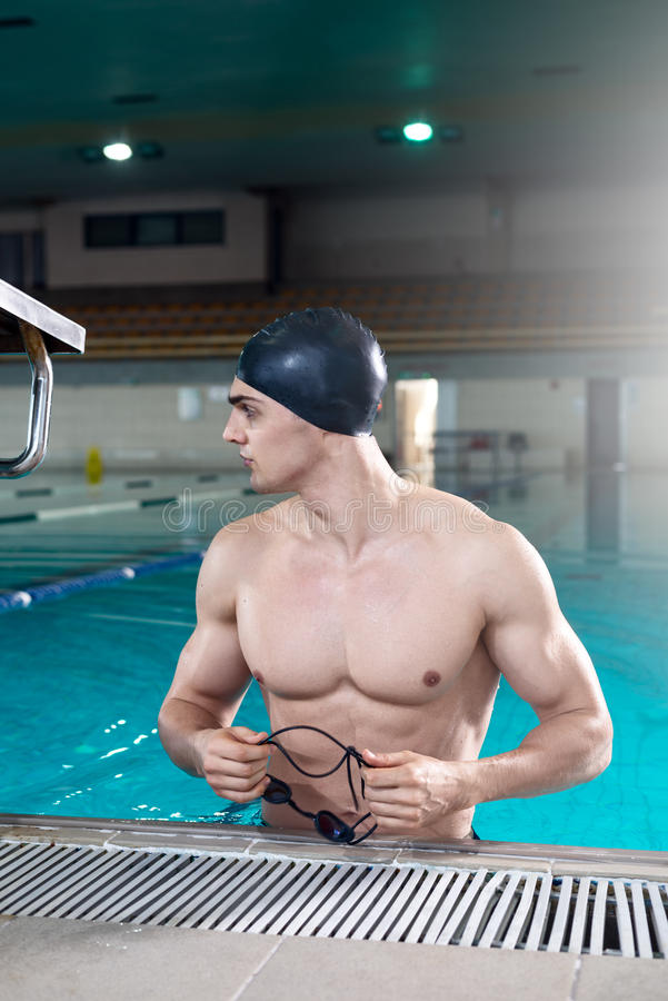 Professional swimmer after the training. Holding the goggles, looking on the side. Artificial lens flare, copy space stock photo