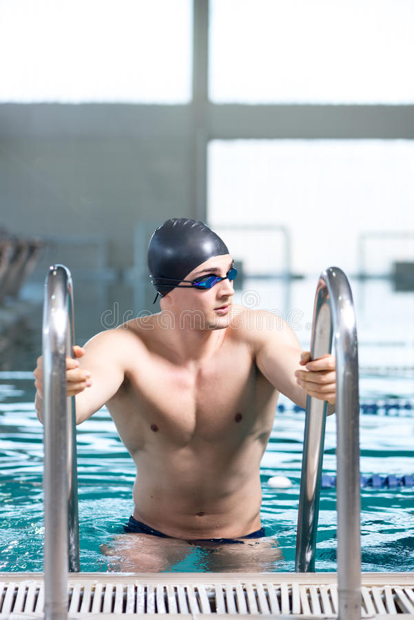 Professional swimmer using ladder. Professional swimmer after the race, using ladder, exiting the pool. Looking away from the camera, copy space on the top of stock photos