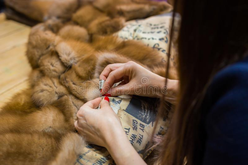 Tailor repairing fur coat. Professional tailor, designer repairing fur coat at atelier, studio. Fashion and tailoring concept royalty free stock photos