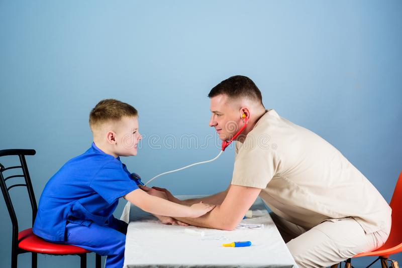 Professional talk. medicine and health. small boy with dad play. Future career. nurse laboratory assistant. family. Doctor. happy child with father with stock photography