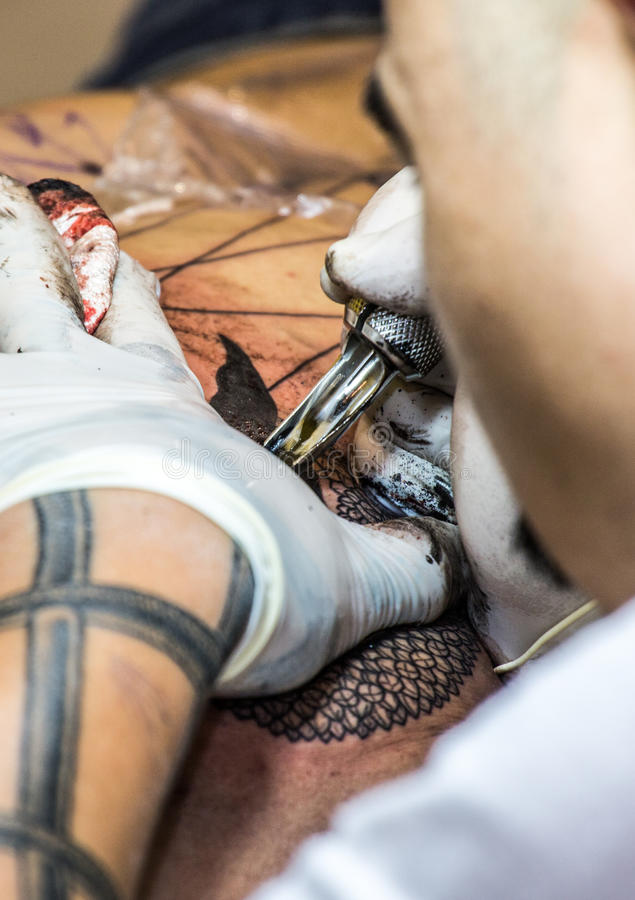 Download Professional Tattoo Artist Makes A Tattoo Editorial Stock Photo - Image: 83710003