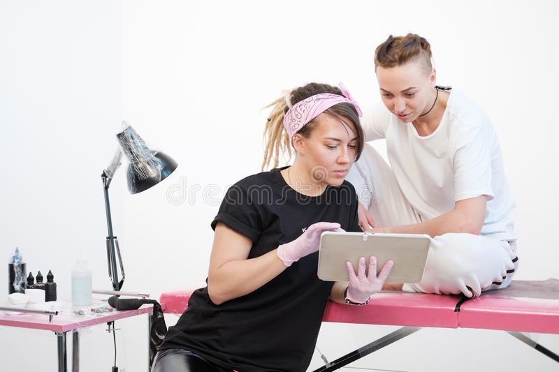 Professional tattoo master woman shows sketches on the tablet to the client girl. Discussion future tattoos. royalty free stock photos