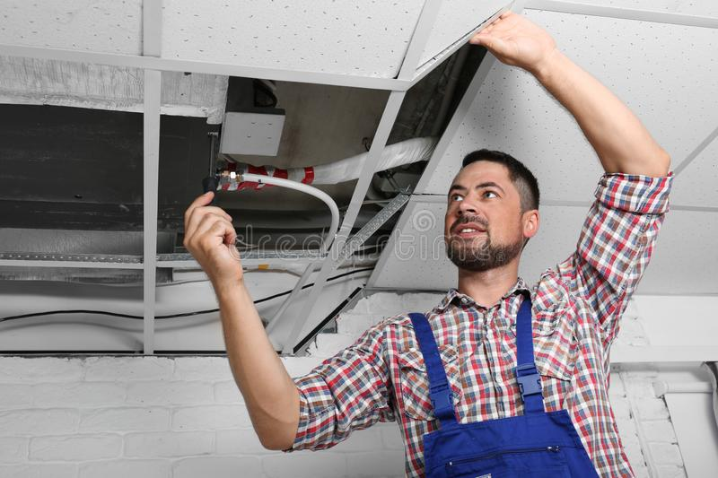 Professional technician repairing ceiling mounted air conditioner stock photos
