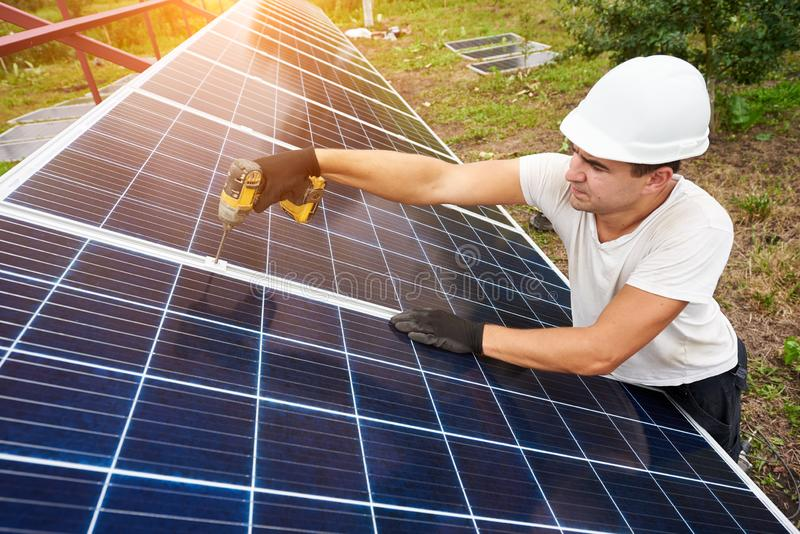 Installation of stand-alone exterior photo voltaic panels system. Renewable green energy generation. Professional technician working with screwdriver connecting royalty free stock image