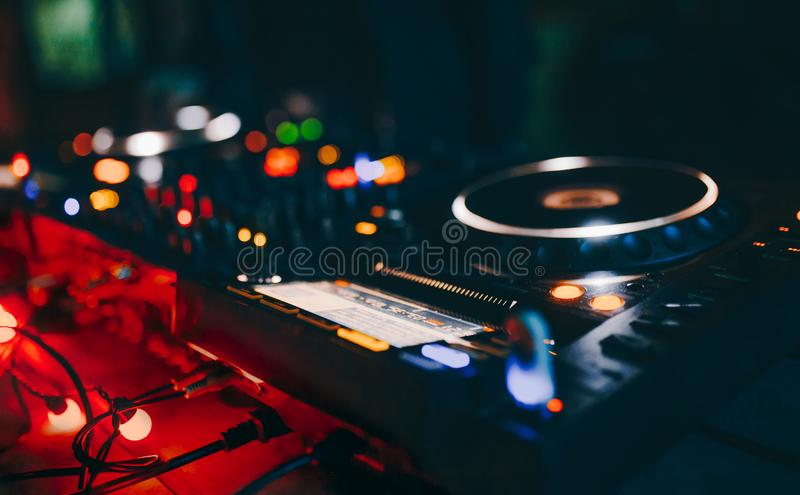 Professional techno rave minimal urban light concert dj turntables player PIONEER device with sound mixer panel and jog wheel.Club royalty free stock photography
