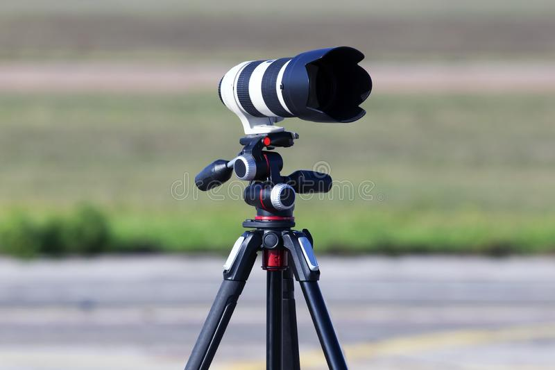 Professional telephoto lens for DSLR camera on the tripod stock image