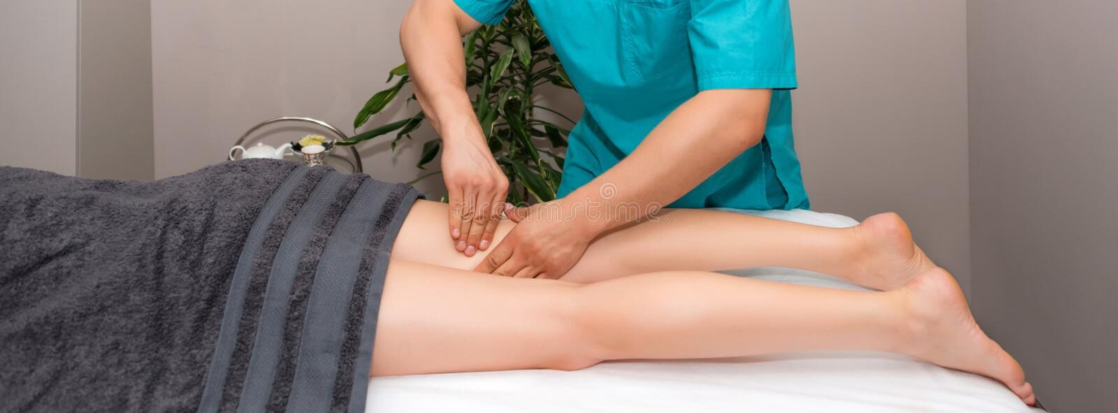 Professional therapist giving relaxing leg massage treatment to a woman in spa. Relaxing spa procedures, whole body. Massage. Pleasure, rest, body care, beauty stock image