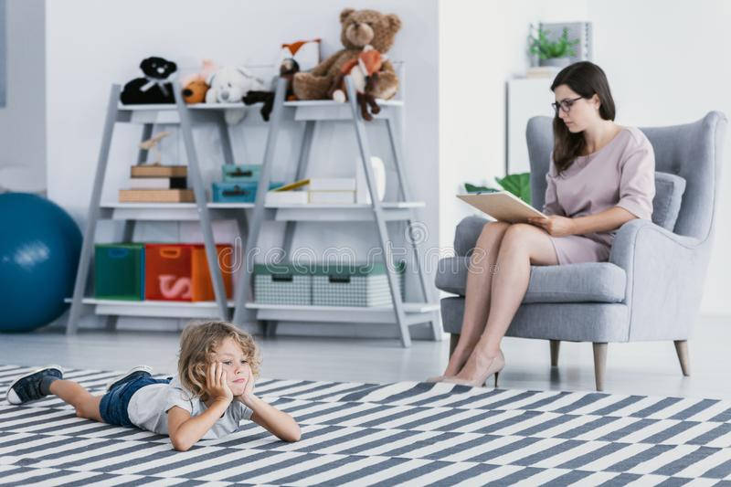 A professional therapist making a diagnose of a withdrawn child that is lying on the floor in a psychology office. stock photography