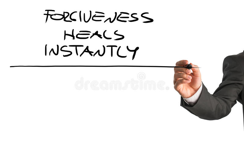Professional therapist writing a Forgiveness heals instantly say royalty free stock image