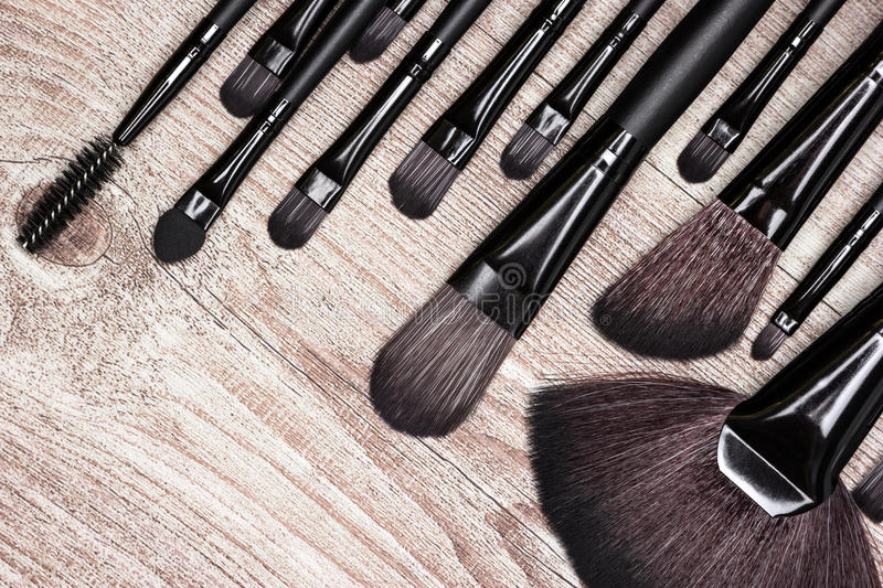 Professional tools of makeup artist on shabby wooden surface. Set of various natural bristle makeup brushes: for applying foundation, blush, eyeshadow, fan brush royalty free stock image