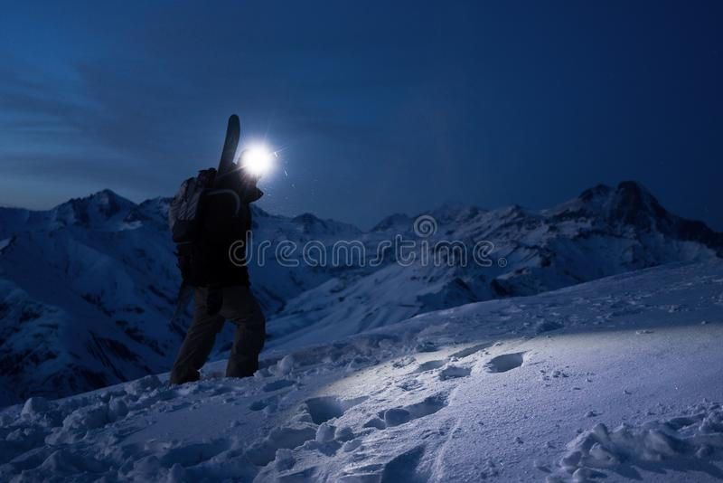 Professional tourist commit climb on great snowy mountain at night. Wearing backpack, headlamp and ski wear. Backcountry. stock photos