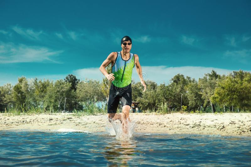 Professional triathlete swimming in river`s open water. Man wearing swim equipment practicing triathlon on the beach in summer`s day. Concept of healthy stock photo