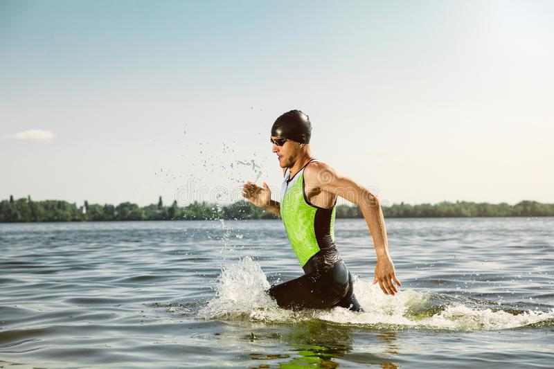 Professional triathlete swimming in river`s open water. Man wearing swim equipment practicing triathlon on the beach in summer`s day. Concept of healthy stock photography