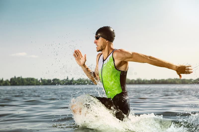Professional triathlete swimming in river`s open water. Man wearing swim equipment practicing triathlon on the beach in summer`s day. Concept of healthy royalty free stock images