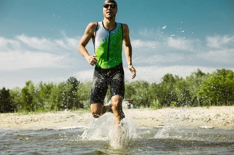 Professional triathlete swimming in river`s open water. Man wearing swim equipment practicing triathlon on the beach in summer`s day. Concept of healthy royalty free stock photos