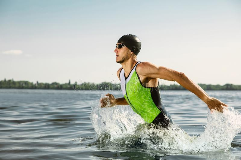 Professional triathlete swimming in river`s open water. Man wearing swim equipment practicing triathlon on the beach in summer`s day. Concept of healthy royalty free stock image