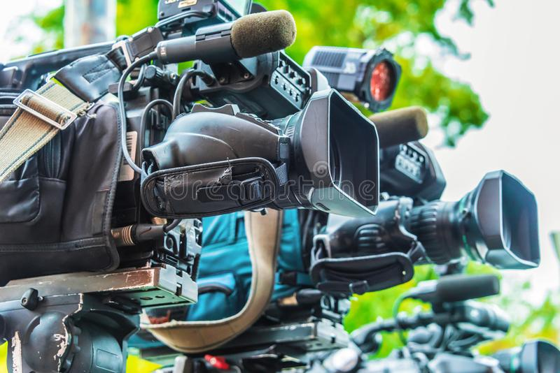 Professional tv cameras on tripods recording social event. On the street stock photography