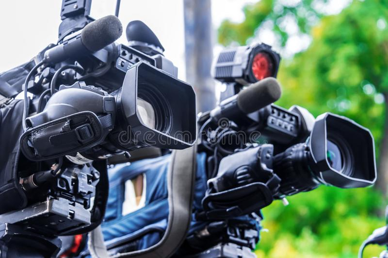 Professional tv cameras on tripods recording social event. On the street stock image