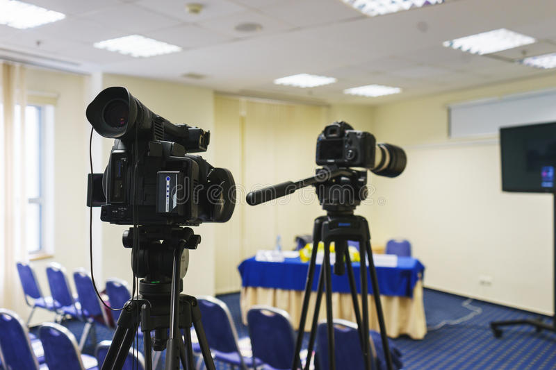 Professional video camera mounted on a tripod to record video during a press conference, an event, a meeting of journalists. stock photo
