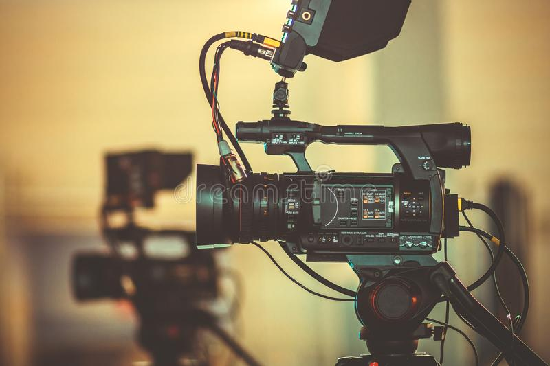 Professional video camera stands on a tripod, the process of filming a movie from different angles stock images