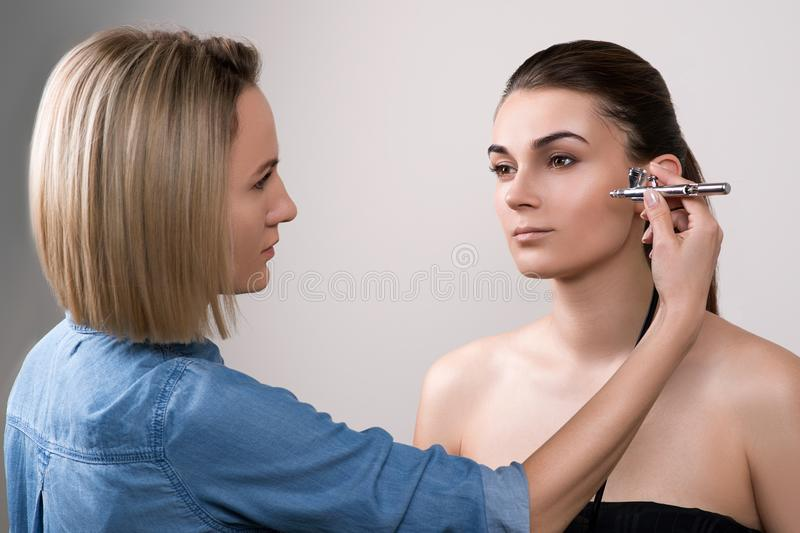 Professional visagist doing makeup and using airbrush. Girl doing makeup in beauty salon. Fashion brunette model with hair tail ov stock image
