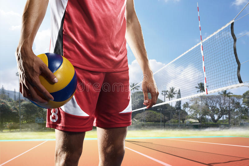 Professional volleyball player with ball on the court stock image
