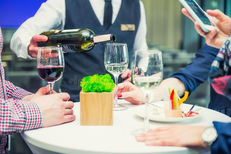 Professional waiter in uniform serving wine to guests of event. Catering or celebration concept. Service at business, corporate me stock photos