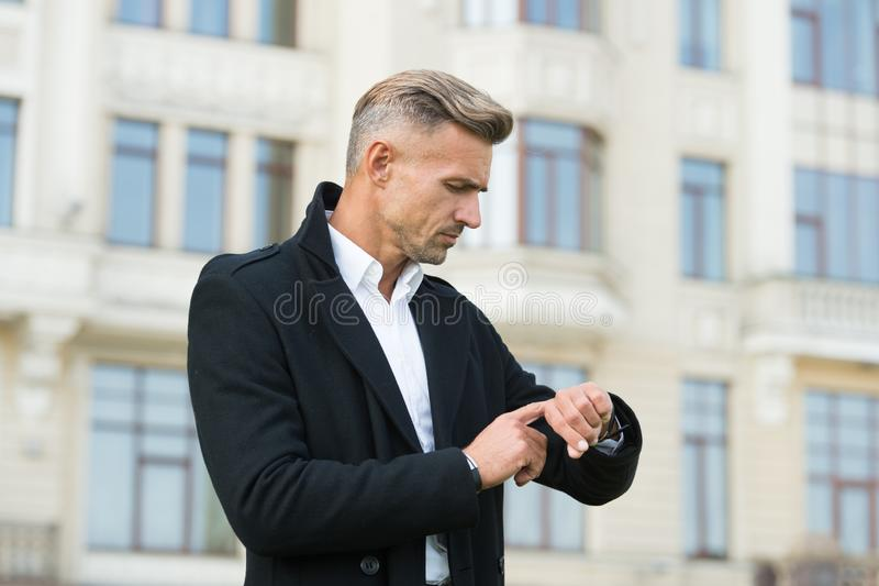 Professional watch ideal for leading business lifestyle. Businessman check time by watch. Handsome man use wrist watch. Outdoor. Reliable watch. Stylish royalty free stock photography