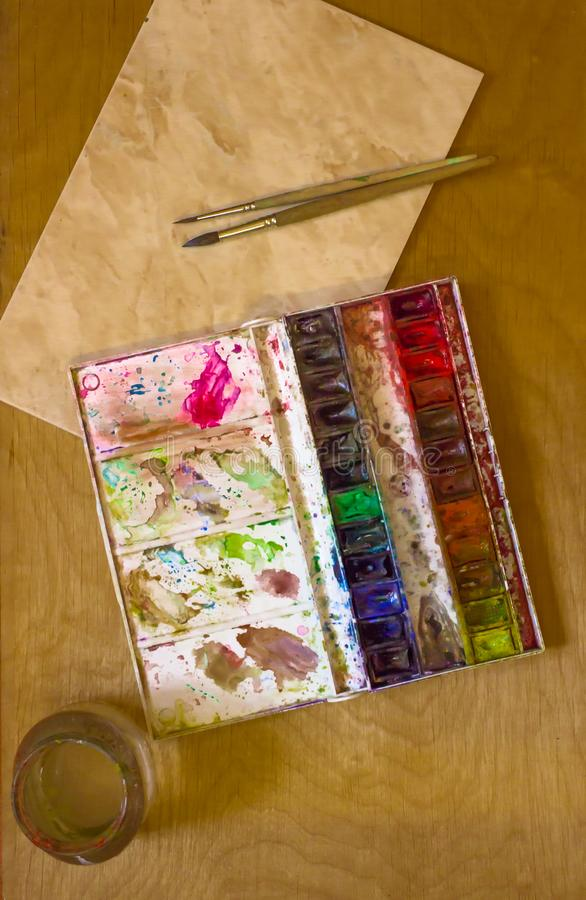 Professional watercolor aquarell paints in box with brushes on old wooden board. Professional dirty watercolor aquarell paints in box with brushes, palette and royalty free stock images