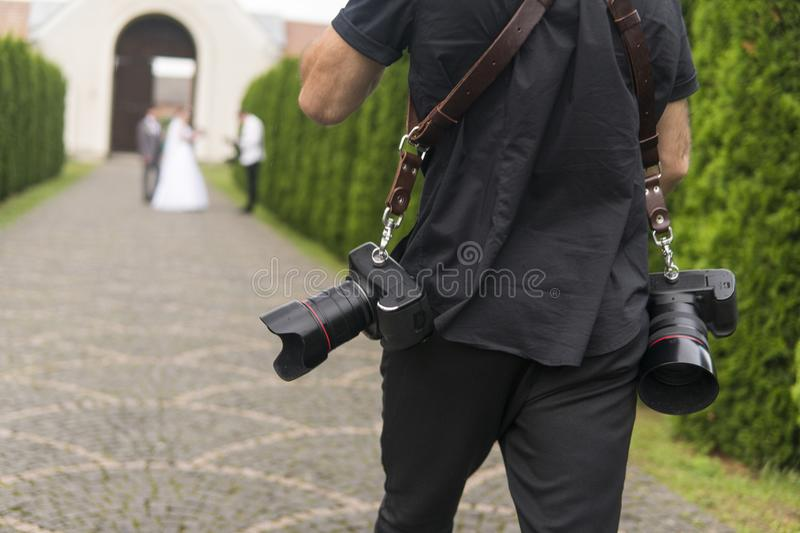 Professional wedding photographer takes pictures of the bride and groom in garden, the photographer in action with two. Cameras on a shoulder straps stock image