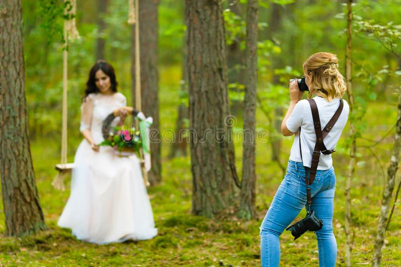 Professional wedding photographer taking close-up portraits of the bride. On a rope swing with rustic style bridal bouquet stock photos