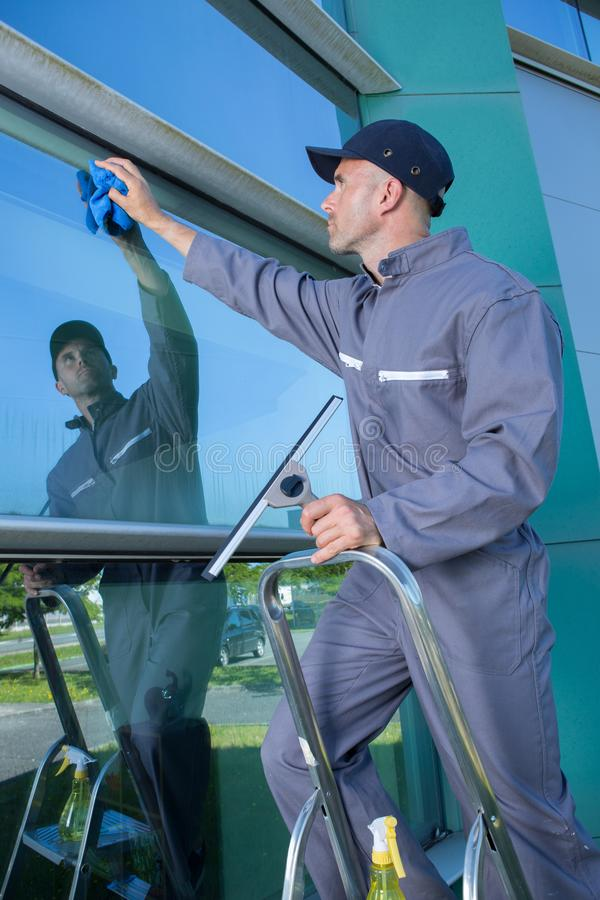 Professional window cleaner at work outdoors royalty free stock photo