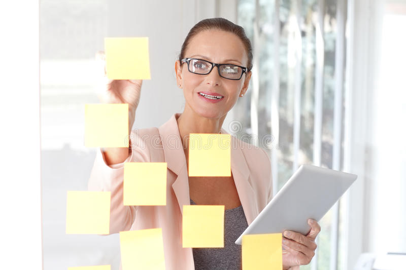 Professional woman brainstorming at office. Portrait of middle aged businesswoman holding digital tablet in her hand while standing at office in front royalty free stock image