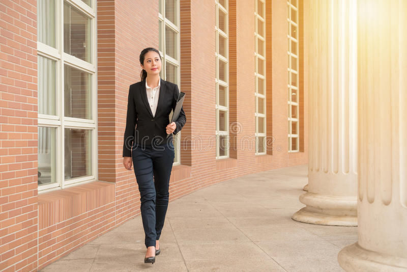 Professional woman lawyer walking in court outdoor. Corridor looking at the sun thinking about future legal direction after completion case meeting leisure time royalty free stock photography