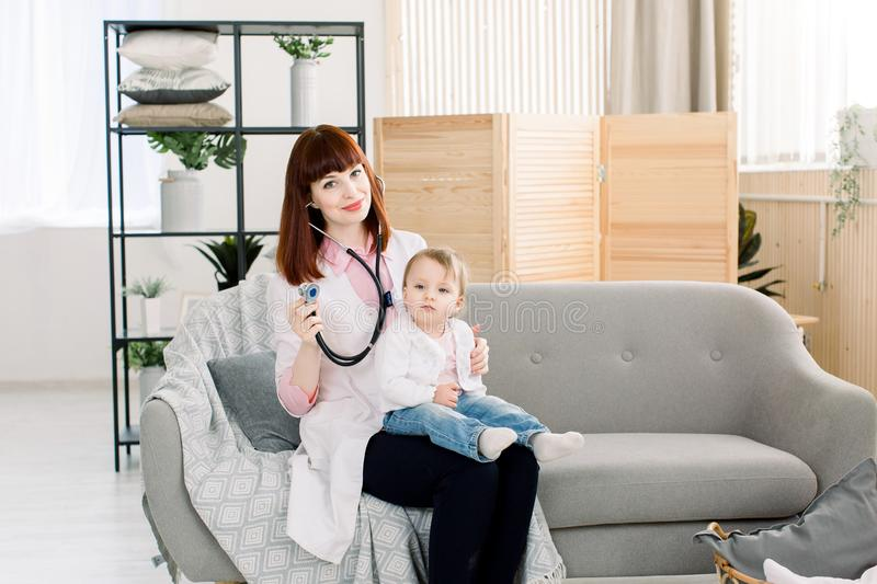 Professional woman pediatrician examining little baby girl by stethoscope. Doctor and baby sitting on gray sofa in stock images