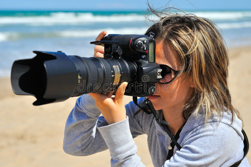 Professional woman photographer. On the beach royalty free stock photography