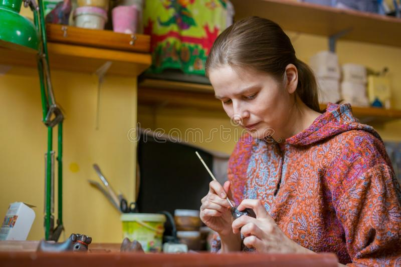 Professional woman potter painting ceramic souvenir penny whistle in pottery. Professional woman potter, decorator painting ceramic souvenir penny whistle toy stock image