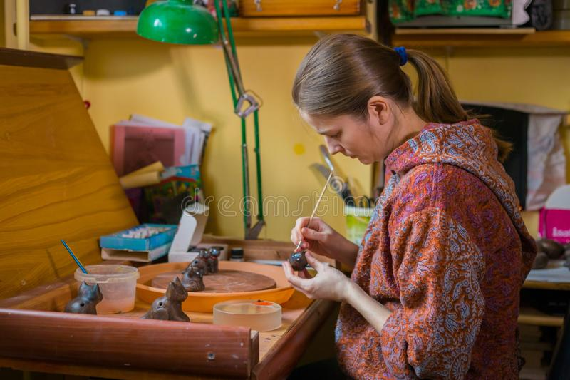 Professional woman potter painting ceramic souvenir penny whistle in pottery. Professional woman potter, decorator painting ceramic souvenir penny whistle toy royalty free stock photography