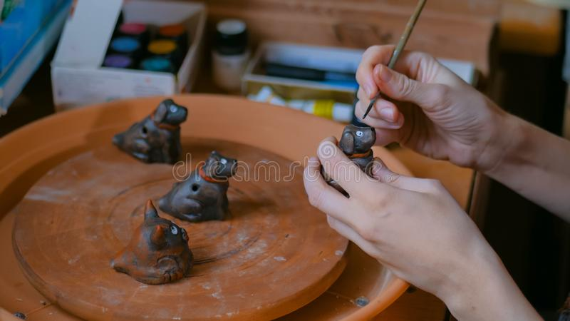 Professional woman potter painting ceramic souvenir penny whistle in workshop royalty free stock image