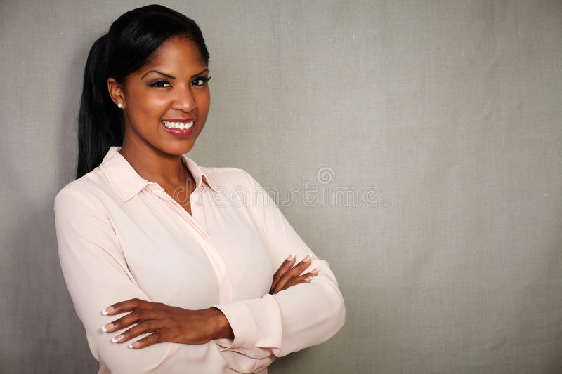 Professional woman smiling with arms crossed royalty free stock image