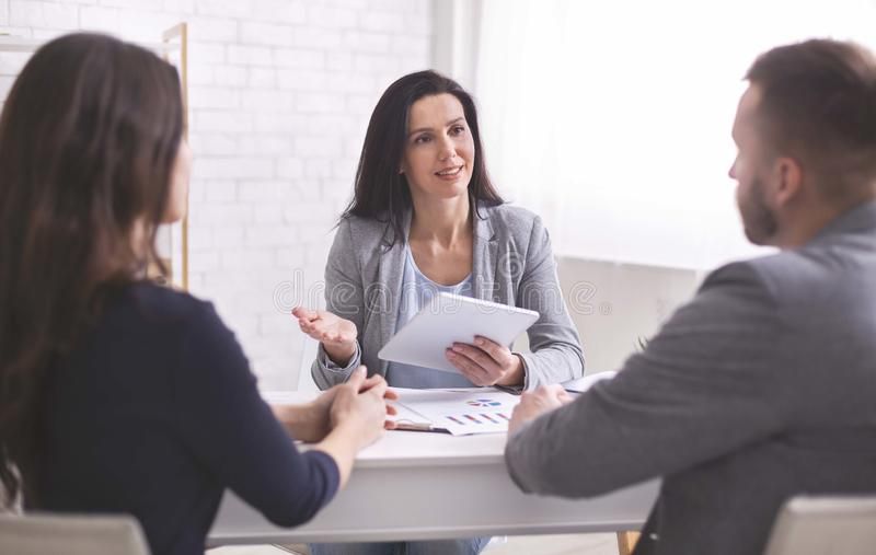 Professional woman talking to young couple at personal meeting royalty free stock image