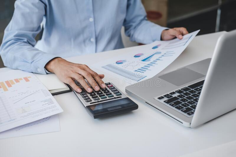 Professional at work, business woman working and analyzing on laptop with calculate statistics of financial document data graph stock photo