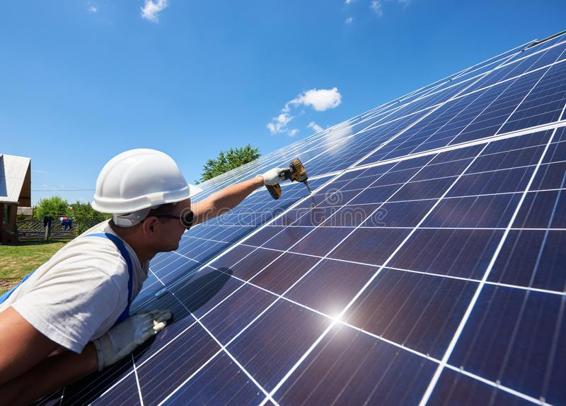 Professional worker installing solar panels on the green metal construction. Using different equipment, wearing helmet. Innovative solution for energy solving stock photos