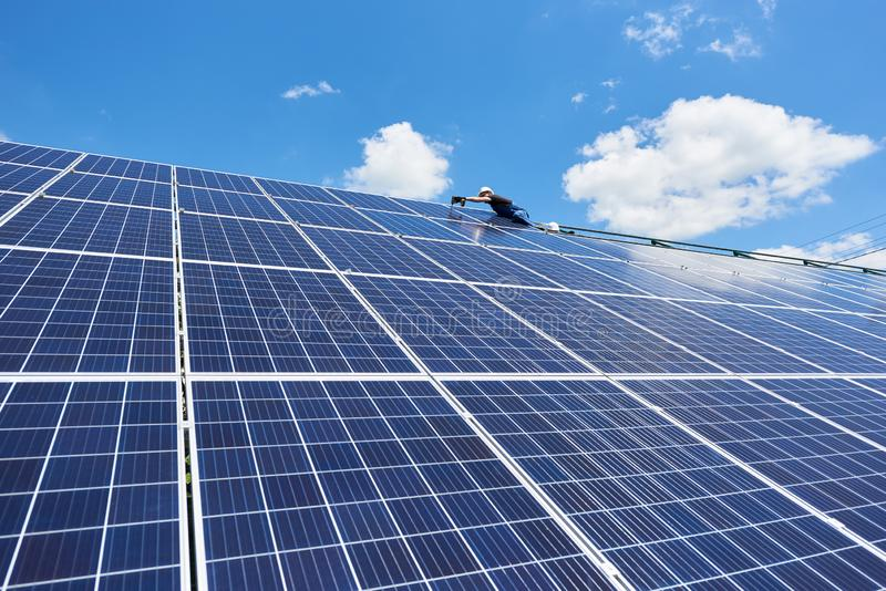 Professional worker installing solar panels on the green metal construction stock images