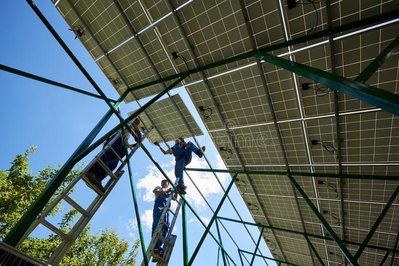 Professional worker installing solar panels on the green metal construction stock photography