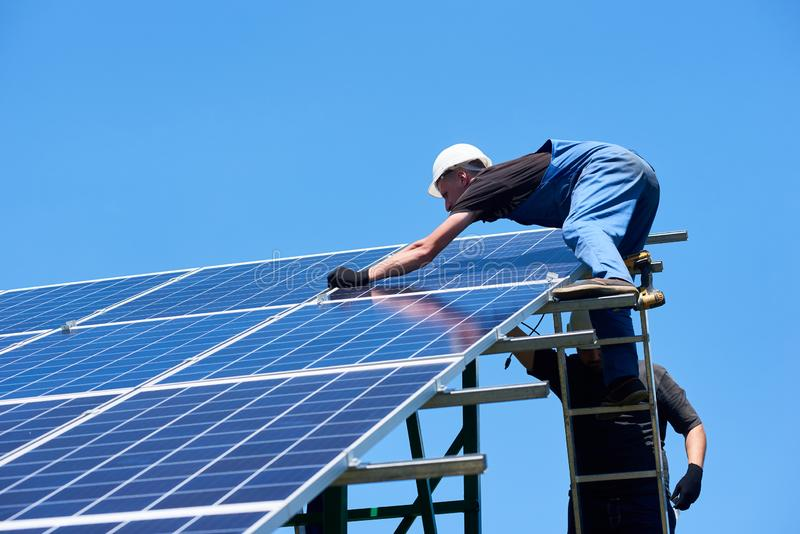 Professional worker installing solar panels on the green metal construction royalty free stock image