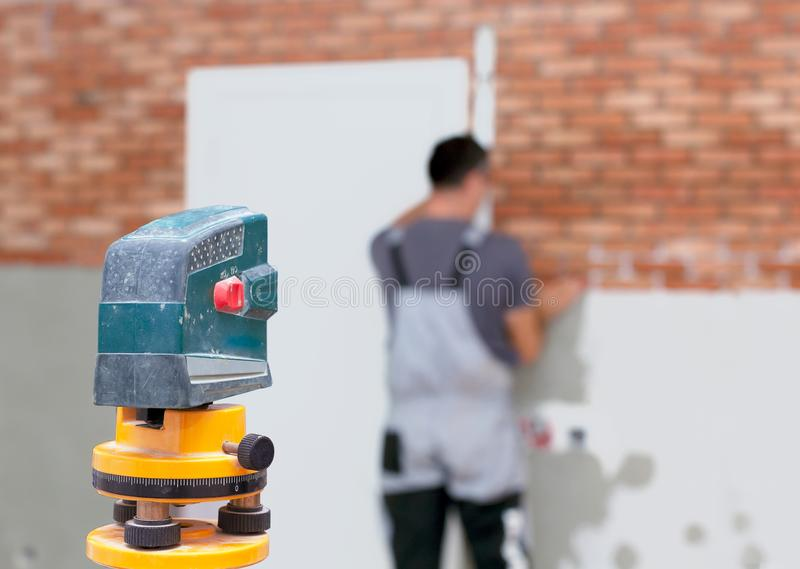 Professional worker lays bricks on the wall using laser level stock image