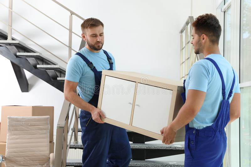 Professional workers carrying cabinet at stairs. Moving service royalty free stock photos