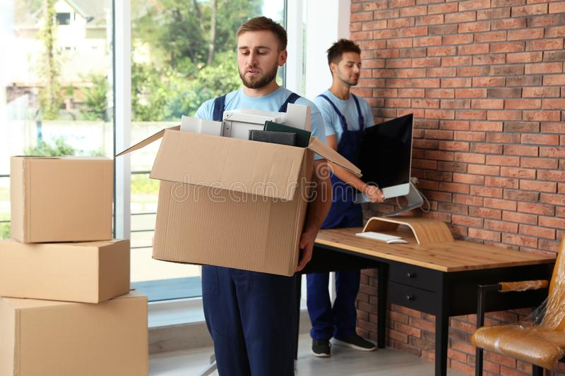 Professional workers carrying stuff. Moving service royalty free stock image